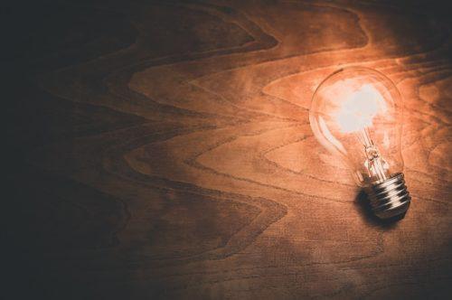 机の上で弱く光る電球の画像