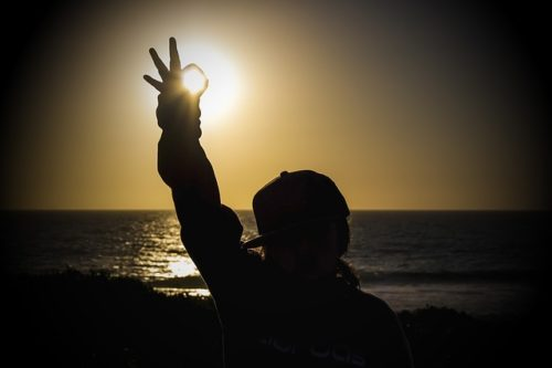 夕日をバックにOKポーズをする女性の画像