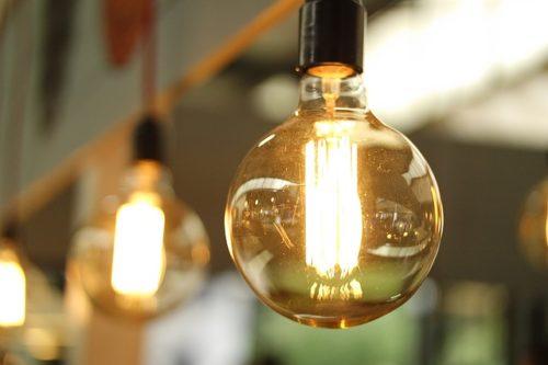 光が灯った電球の画像