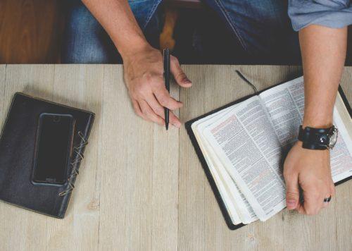ペンを片手に本を開く人