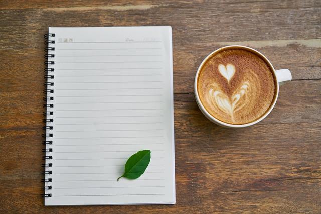 ノートとその上に置かれた葉っぱ、カフェラテ