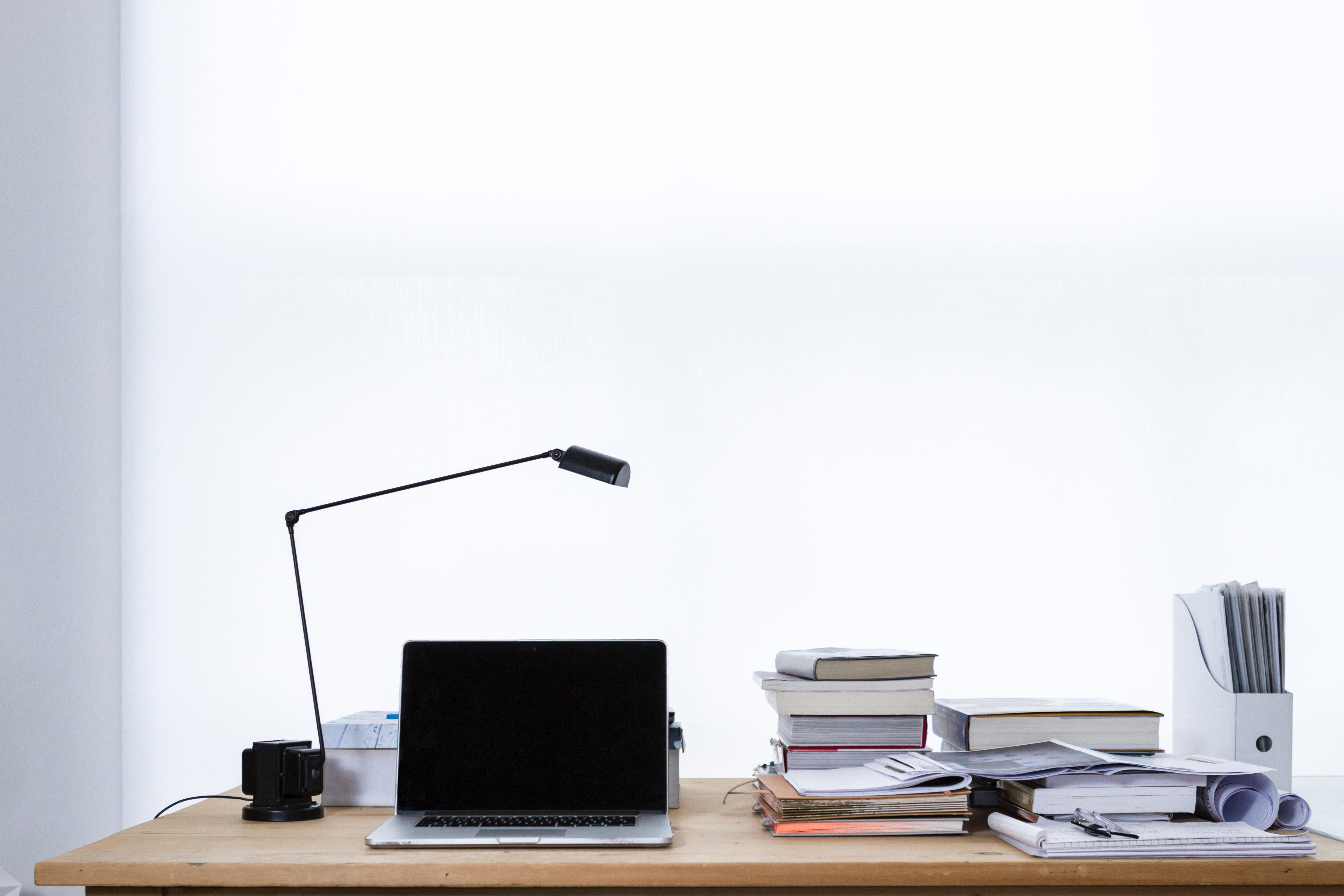 PCと本、電気スタンドが置かれた机