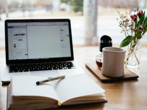 PCとマグカップ、手前には開かれたノート