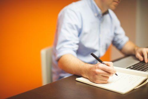 PCを見ながら何かを書く男性
