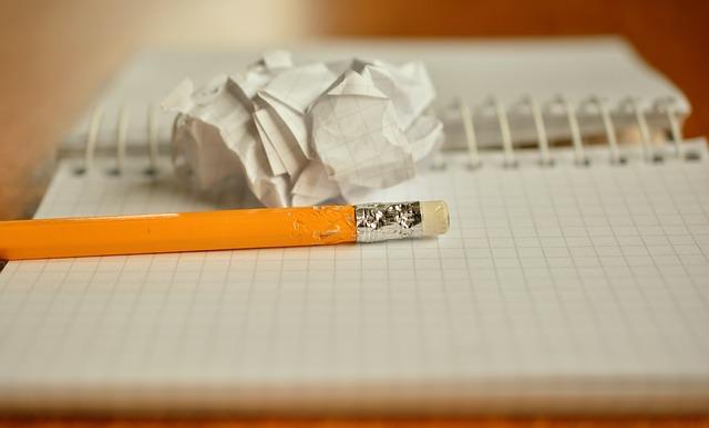 鉛筆とノートと丸めた紙