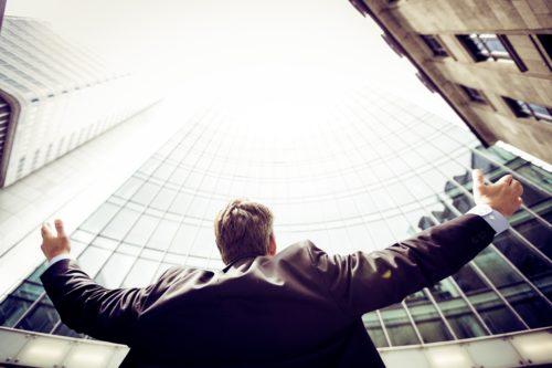 上を向いて両手を上げる男性