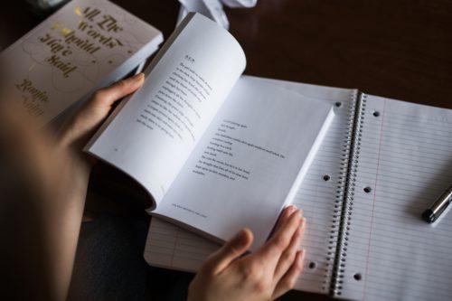 ノートを広げながら本を開く人