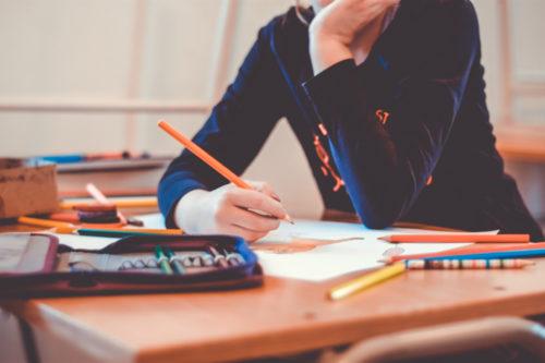散らかった机で勉強している様子