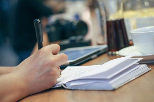 小さなノートに何かを書き込む様子