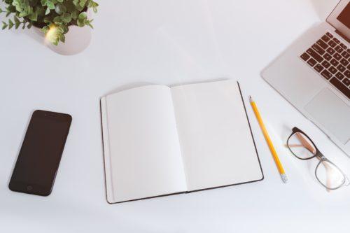 白紙の広げたノート、スマホ、鉛筆、眼鏡の画像