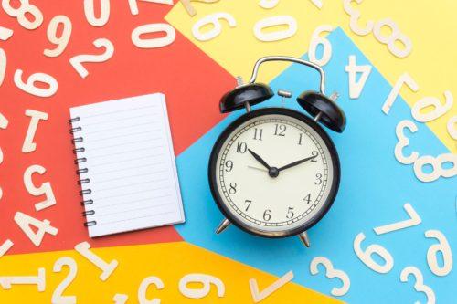 数字と時計とノートの画像