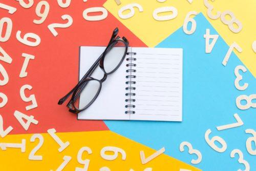 数字と眼鏡とノートの画像