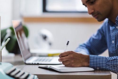 パソコンを開いてノートにメモを取る男性