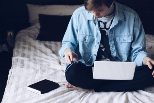 ベッドでパソコンを開きつつイヤホンをする男性