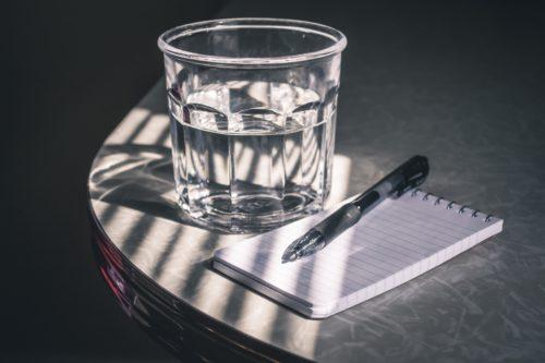 水が入ったコップとペンが並んでいる画像
