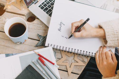 誰かがノートに何かを書いている画像