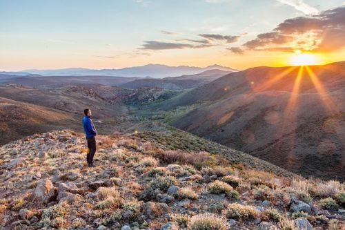 山の上から夕陽を見る男性