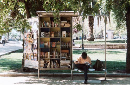 屋外で本を売る男性の画像