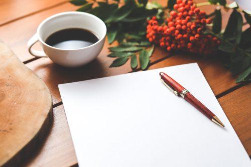 紙+ペン+コーヒー+赤い木の実の画像