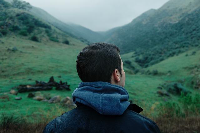 草が生い茂る山を見上げる男性の後ろ姿