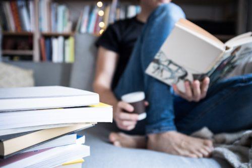 飲み物片手に読書をしている人の画像