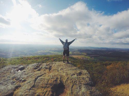 山頂でピースサインをする男性