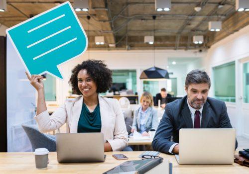 パソコンをいじる男性とフキダシを持って微笑む女性