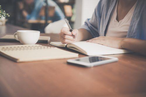 ノートを広げて勉強している人の画像