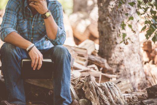 本を片手に木材の上に座る男性