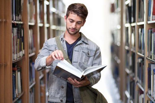 図書館で本を立ち読みする男性の画像