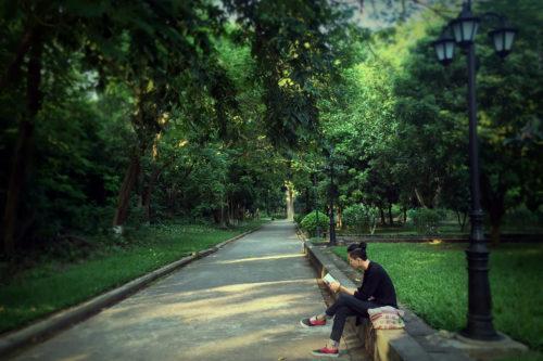 道端に腰かけて読書する男性